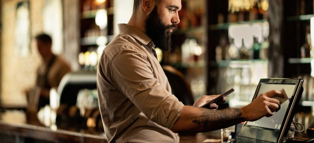 Young barista going through orders while working at cash register in a bar.